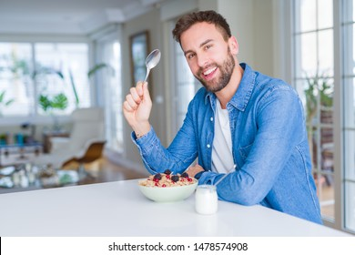 Handsome man having breakfast eating cereals at home and smiling