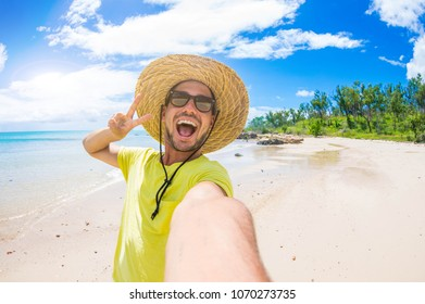 Handsome man having fun taking a selfie at the tropical island at holiday