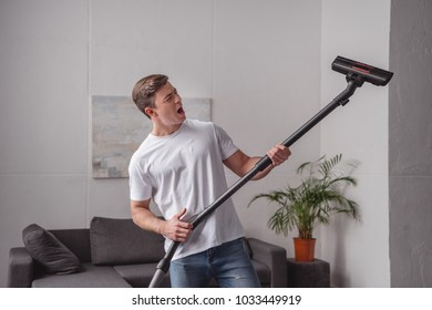 handsome man having fun with vacuum cleaner in living room