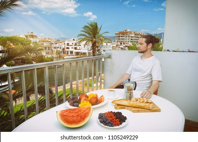 Handsome man having healthy breakfast on hotel terrace with beautiful view of the resort. Empuriabrava, Spain. Vegan food concept