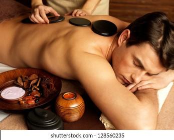 Handsome man having stone massage in spa salon. Healthy lifestyle.