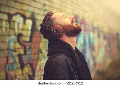 Handsome man in headphones listening to music outdoors - Shutterstock ID 521956912