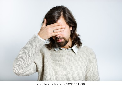 Handsome man hides eyes, with long hair, isolated studio photo