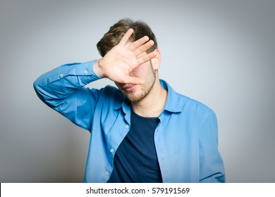 Handsome man hides face with his hands, isolated on a gray background