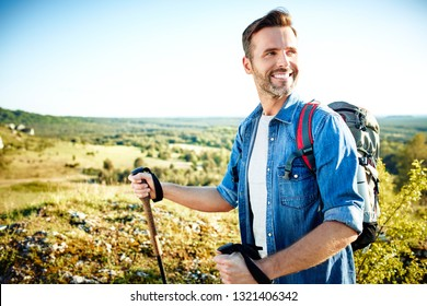 Handsome man hiking with poles and backpack during sunny day