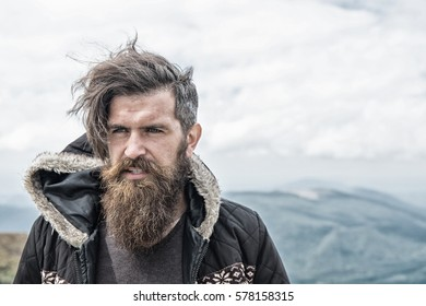 Handsome man hipster or guy with beard and moustache on serious face in hat and jacket outdoor on mountain top against cloudy sky on natural background, copy space
