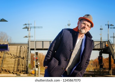 handsome man in his 50s waiting at train station