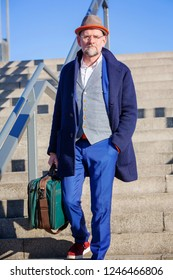 handsome man in his 50s walking down stairs with his suitcase