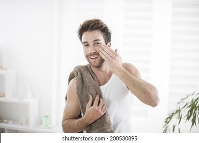 handsome man in his bathroom towel on shoulders