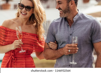 Handsome man with his beautiful girlfriend with glass of wine together. Beautiful couple enjoying together.