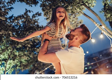 Handsome man with his little cute daughter are spending time together in park in the evening. Dad and daughter having fun and smiling outdoors on a terrace with garland of light bulbs.