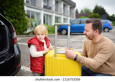 Handsome man and his little son going to vacations, loading their suitcase in car trunk. Automobile trip in the countryside. Roadtrip for family with little kids
