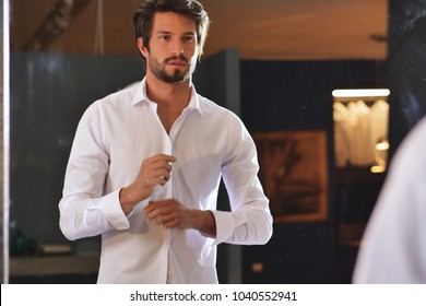 A handsome man in his loft dresses his sexy white shirt , looks into his room and smiles with a sure look at himself. Concept of: elegance, business, work