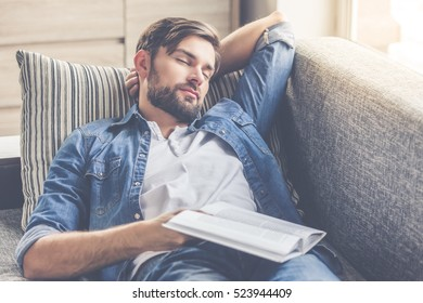Handsome man is holding a book and napping while lying on couch at home