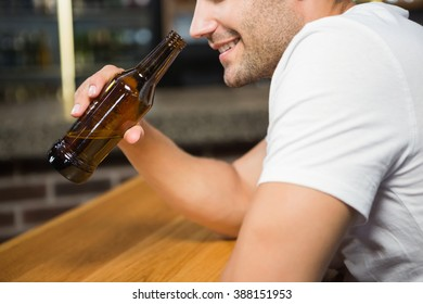 Handsome man holding a bottle of beer in a pub