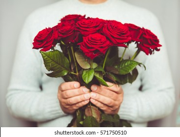Handsome man holding Bouquet of beautiful red roses in hand. 8 march