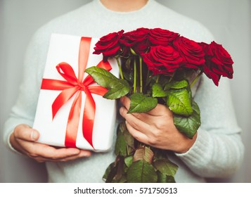 Handsome man holding Bouquet of beautiful red roses in hand, 8 march woman day