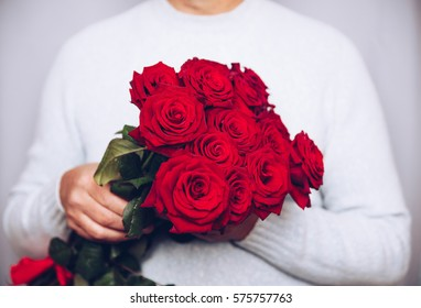 Handsome man holding Bouquet of beautiful red roses in hand, Present for 8 march