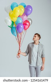 handsome man holding bundle of colorful balloons on grey background