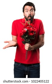 Handsome man holding flowers making unimportant gesture over white background