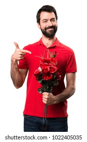 Handsome man holding flowers presenting over white background
