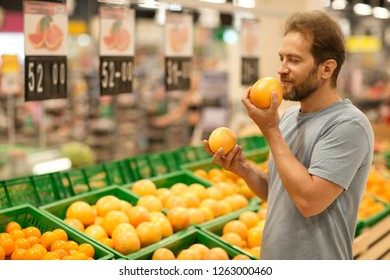 Handsome man holding grapefruits in hands and smelling. Happy facial expression with closed eyes of customer. Bearded man do shopping in supermarket and choosing fresh fruit.
