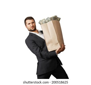 handsome man holding heavy paper bag with money. isolated on white background