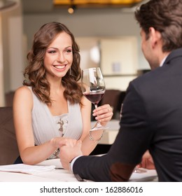 Handsome man holding his girlfriend hand. Drinking wine and smiling