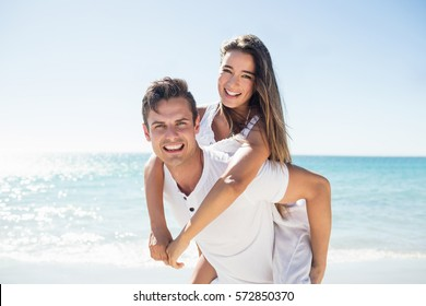 Handsome man holding his girlfriend on the beach