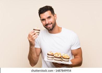 Handsome man holding muffin cake over isolated background