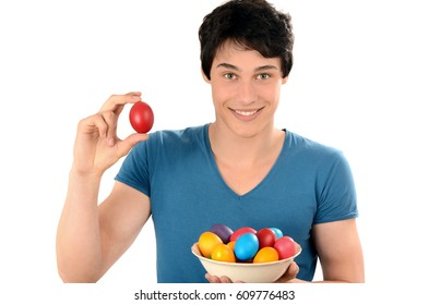 Handsome man holding up a red Easter egg and a basket with colorful dyed eggs. Young man smiling with a red egg in the hands.  Isolated on white background. Happy Easter!