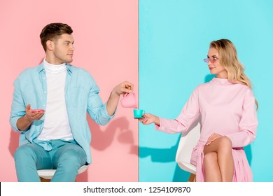 handsome man holding toy milk jug while woman holding coffee cup on pink and blue background