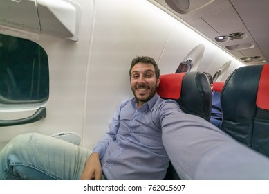 Handsome man in holiday take selfie photo on the air plane during flight around the world