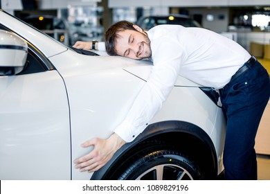 Handsome man is hugging his new car in showroom