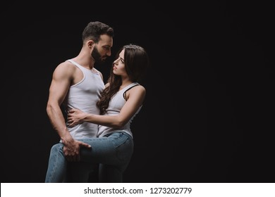 handsome man hugging woman in white singlet isolated on black