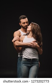 handsome man hugging young woman in white singlet isolated on black
