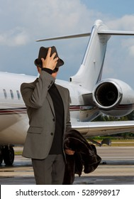Handsome man incognito near a private jet looking down.