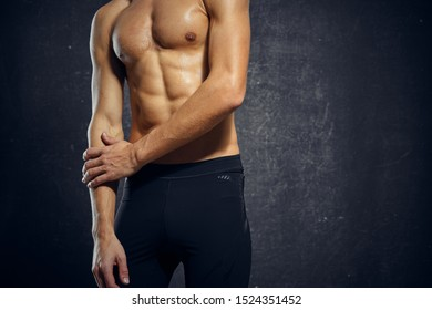 Handsome man with inflated torso bare shoulders black leggings muscle fitness