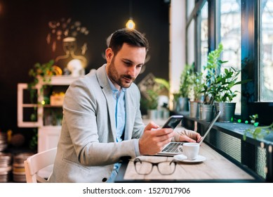Handsome man with injured hand chatting on mobile phone while sitting front of laptop in the cafe.