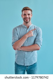 Handsome man isolated. Stylish young man posing on blue background and pointing to the side by fingers..
