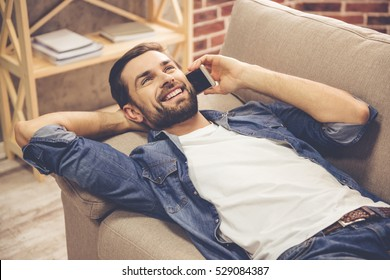 Handsome man in jean clothes is talking on the mobile phone and smiling while lying on couch