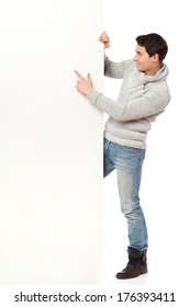 Handsome man in jeans and gray sweater pointing at a banner. Full length studio shot isolated on white.