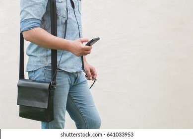 Handsome man in jeans jacket, hipster with shoulder bag stays from the left and holds a phone in hand, photo with no face, white copy space for text from the right