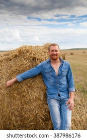 handsome man in jeans on   hay on   field.