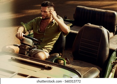 Handsome man in the jeep on the of road