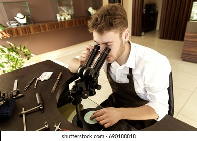 Handsome man Jeweler examines the ring through a microscope sitting at the table with tools to create jewelry in the workshop