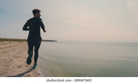 The handsome man jogging on the sea shore