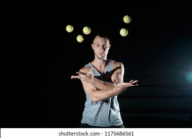 Handsome man juggling balls on black background. Emotional juggler.