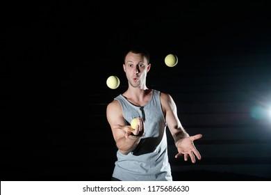 Handsome man juggling balls on black background. Emotional juggler.
