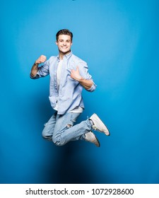 Handsome man jumping isolated on a blue background